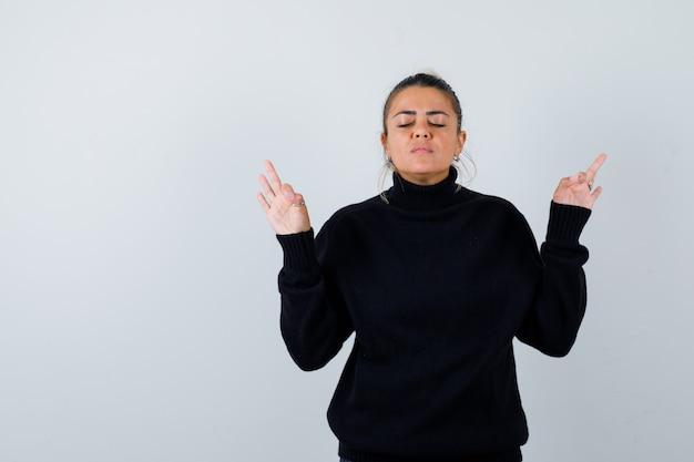 Молодая женщина показывает жест медитации в свитере с высоким воротом и выглядит мирно. передний план.