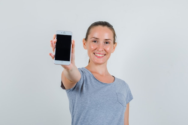 Giovane femmina che mostra il telefono cellulare in maglietta grigia e che sembra gioiosa. vista frontale.