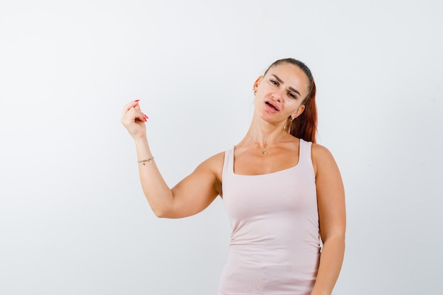 Young female showing money gesture in white tank top and looking puzzled , front view. Free Photo