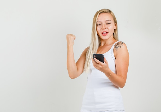 Giovane femmina che mostra il muscolo e che tiene smartphone in singoletto