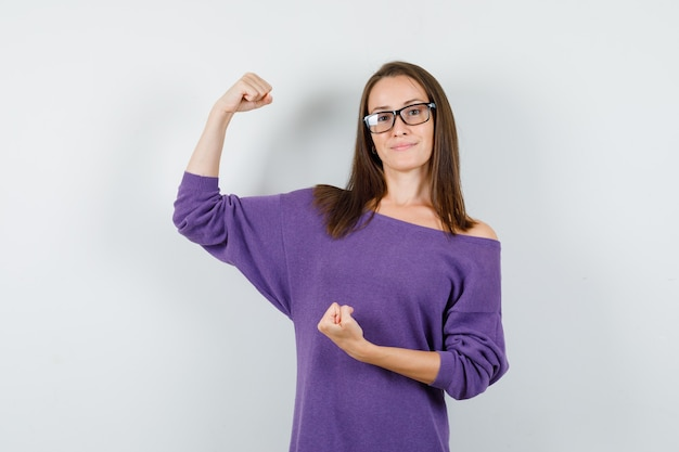 紫のシャツで筋肉と拳を示し、自信を持って見える若い女性。正面図。