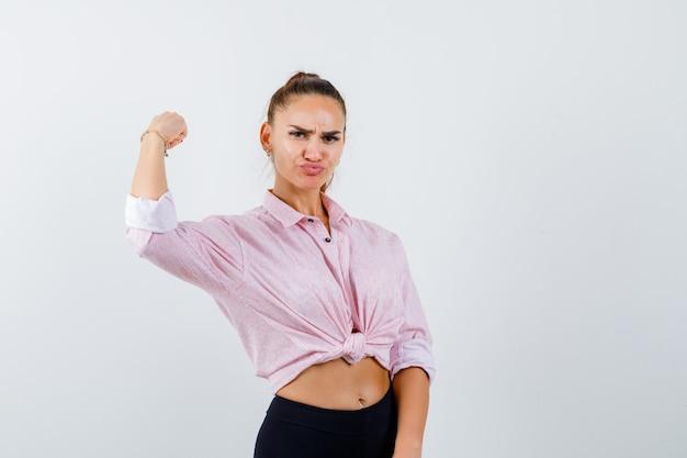 カジュアルなシャツ、パンツで腕の筋肉を示し、自信を持って見える若い女性