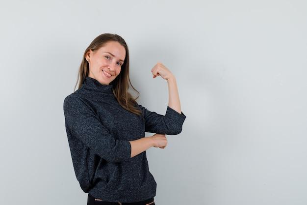 シャツに腕の筋肉を見せ、自信を持って見える若い女性。正面図。