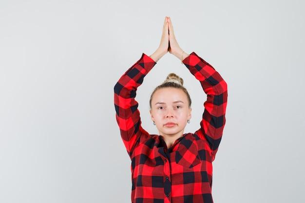 チェックシャツを着て頭上にナマステジェスチャーを示し、自信を持って見える若い女性。正面図。