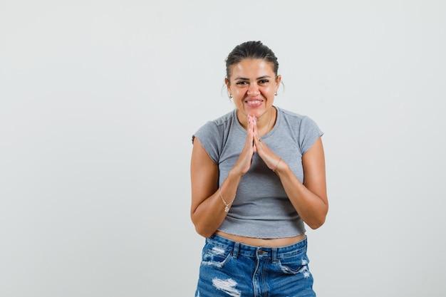 Молодая девушка показывает жест намасте в футболке, шортах и выглядит веселой