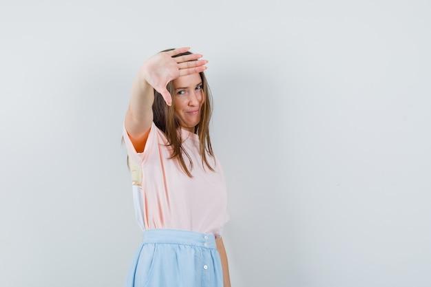 Tシャツ、スカートの正面図でジェスチャーを示さない若い女性。