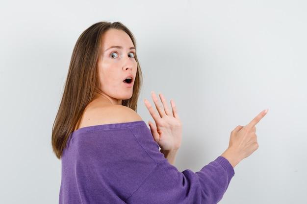 Giovane femmina che non mostra alcun gesto e indica lontano in camicia viola e sembra spaventata. .