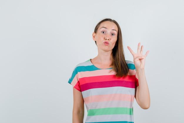 Giovane femmina che mostra il numero quattro in maglietta e che sembra promettente, vista frontale.