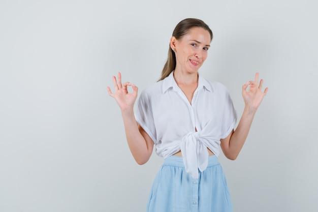 Giovane femmina che mostra gesto giusto in camicetta e gonna e sembra sicura