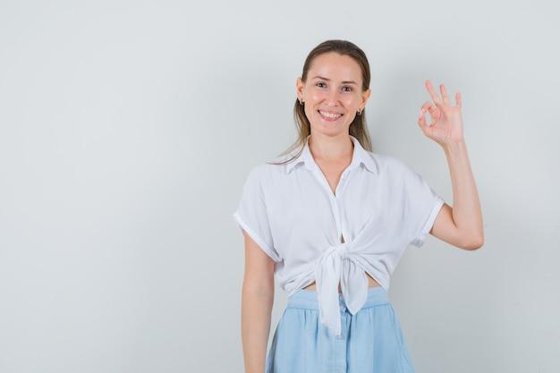 Giovane femmina che mostra gesto giusto in camicetta e gonna e sembra gioviale