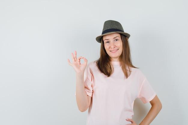 분홍색 티셔츠, 모자에 확인 제스처를 표시하고 자신감을 찾고 젊은 여성. 전면보기.