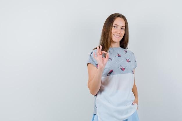 Tシャツ、スカートで大丈夫なジェスチャーを示し、陽気に見える若い女性、正面図。