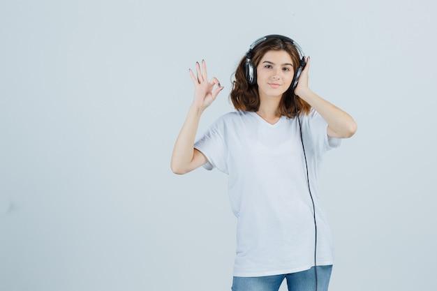 Giovane femmina che mostra gesto giusto mentre ascolta la musica con le cuffie in maglietta bianca e sembra allegra. vista frontale.