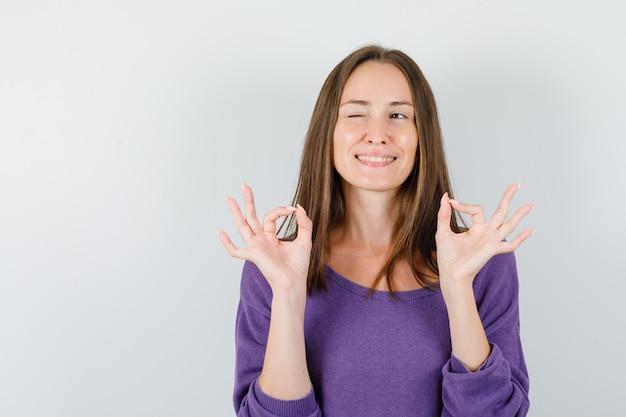 紫色のシャツの正面図でokサインとまばたきの目を示す若い女性。