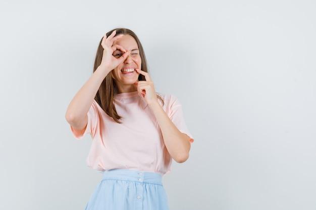 若い女性は、tシャツ、スカート、おかしな顔でokサインを示しています。正面図。