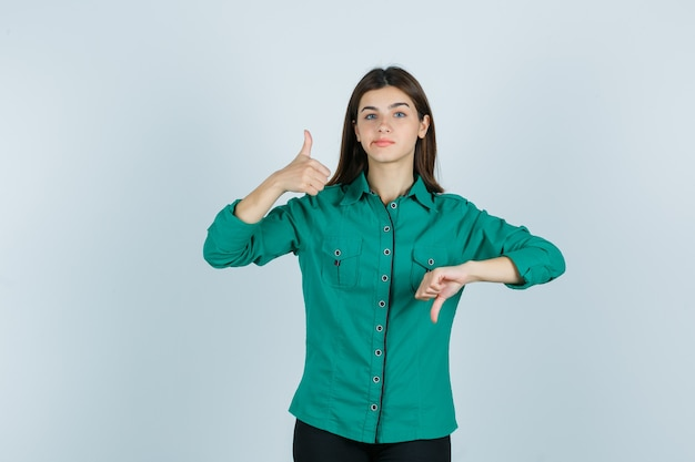 Молодая самка в зеленой рубашке показывает большие пальцы рук, изгибает губы и выглядит нерешительно. передний план.