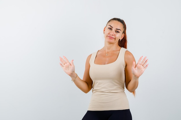 ベージュのタンクトップで降伏ジェスチャーで手のひらを示し、無力に見える若い女性