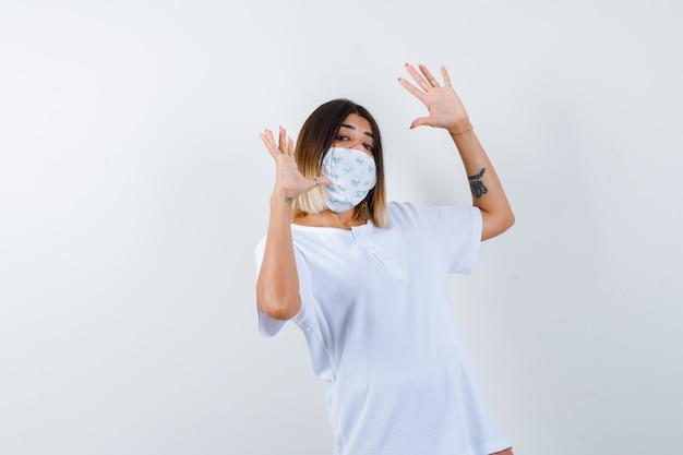 T- 셔츠, 마스크에 항복 제스처에 손바닥을 보여주는 젊은 여성, 무기력, 전면보기.