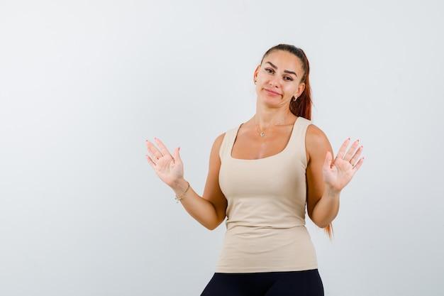 Giovane donna che mostra le palme in gesto di resa in canottiera beige e sembra impotente