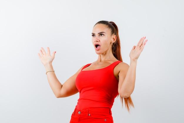 Giovane donna che mostra le palme in gesto di resa in canottiera rossa, pantaloni e guardando perplesso, vista frontale.