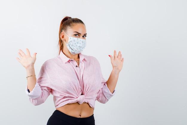 Giovane donna che mostra le palme in gesto di resa in camicia, pantaloni, mascherina medica e sembra impotente. vista frontale.