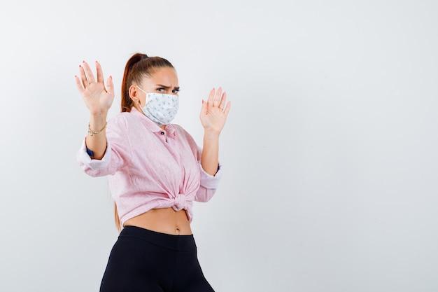 Giovane donna che mostra le palme in gesto di resa in camicia, pantaloni, mascherina medica e che sembra spaventata. vista frontale.