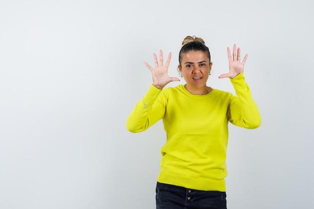 Giovane donna che mostra le palme in maglione, gonna di jeans e sembra sicura