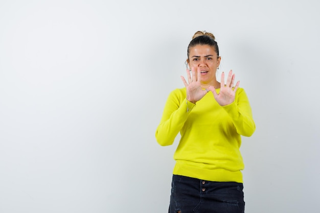 Giovane donna che mostra le palme in maglione, gonna di jeans e sembra carina