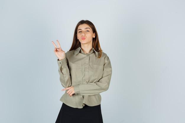 Giovane femmina che mostra il gesto di pace, imbronciato labbra in camicia, gonna e guardando orgoglioso