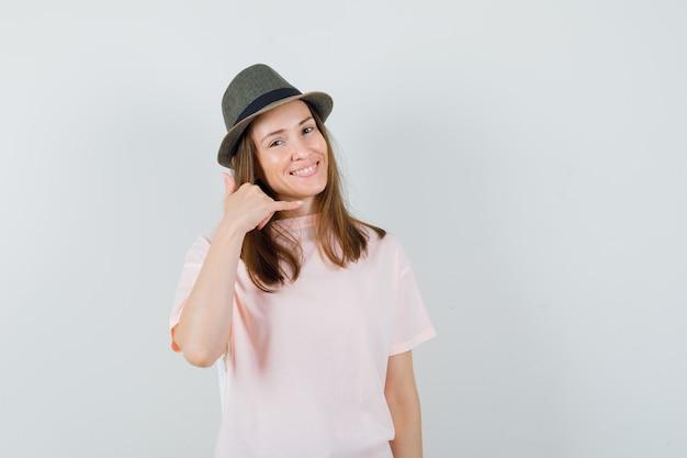 Молодая женщина показывает жест телефона в розовой футболке, шляпе и выглядит полезным, вид спереди.