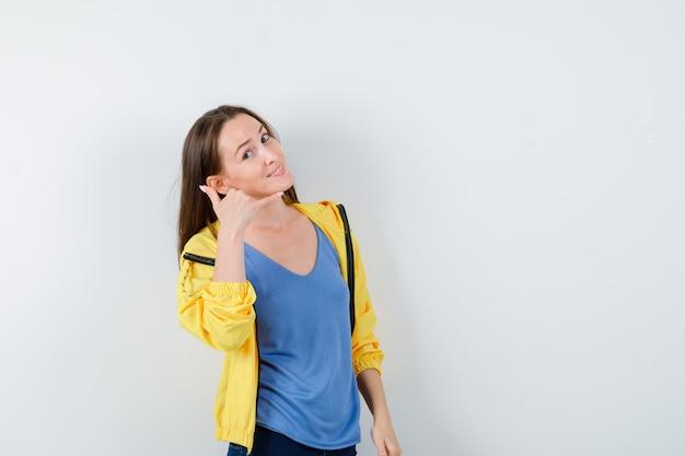 Giovane donna che mostra il gesto del telefono in maglietta e sembra sicura, vista frontale.