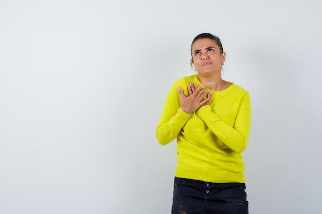 Giovane donna che mostra gesto di preghiera in maglione, gonna di jeans e sembra speranzosa