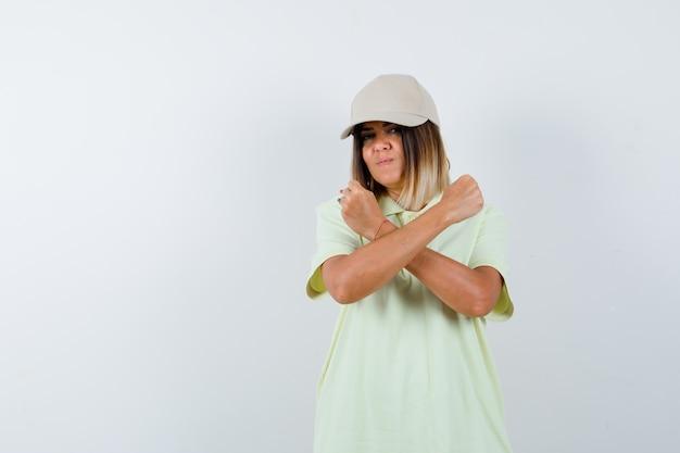 젊은 여성 t- 셔츠, 모자에 항의 제스처를 표시 하 고 심각한, 전면보기를 찾고.