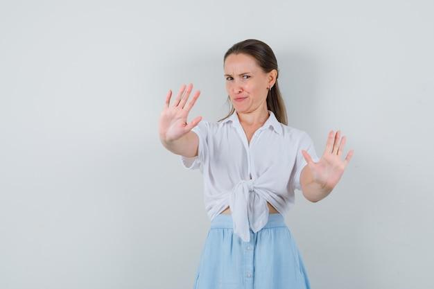 ブラウスとスカートで拒否ジェスチャーを示し、うんざりしているように見える若い女性