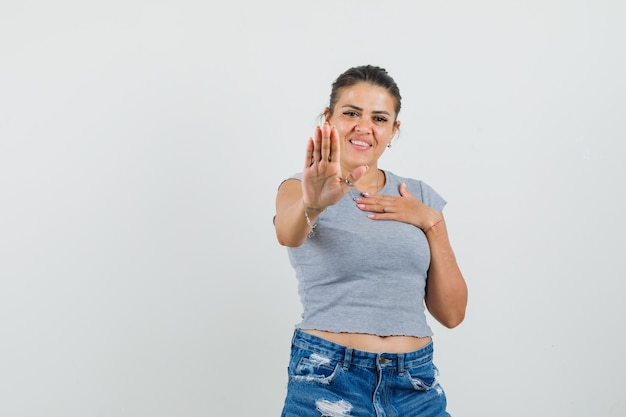 T- 셔츠, 반바지에 거부 제스처를 표시하고 쾌활한 찾고 젊은 여성