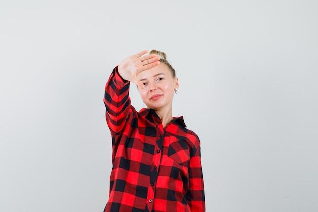 チェックシャツを着て丁寧に拒否ジェスチャーを見せて喜んでいる若い女性。正面図。