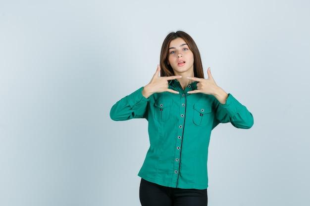 Молодая женщина показывает рок жест в зеленой рубашке и выглядит уверенно, вид спереди.