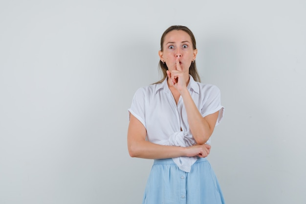 Giovane femmina che mostra gesto di silenzio in camicetta e gonna e guardando attento