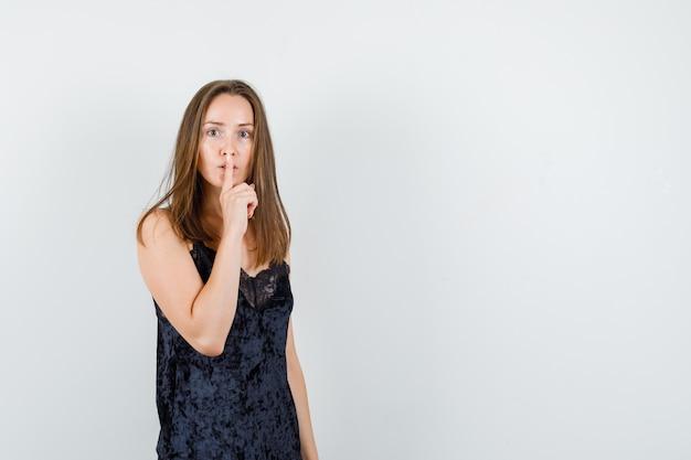 黒の一重項で沈黙のジェスチャーを示し、注意深く見ている若い女性。