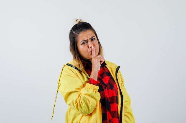 市松模様のシャツ、ジャケットで沈黙のジェスチャーを示し、失望しているように見える若い女性、正面図。