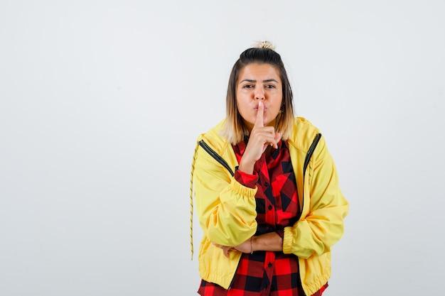 市松模様のシャツ、ジャケットで沈黙のジェスチャーを示し、集中して見える若い女性。正面図。