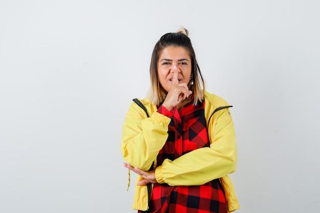 체크무늬 셔츠, 재킷을 입고 명랑한 표정을 짓고 앞모습을 바라보며 침묵의 몸짓을 하는 젊은 여성.