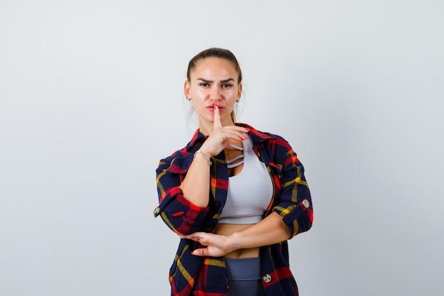 クロップトップ、市松模様のシャツ、パンツで沈黙のジェスチャーを示し、真剣に見える若い女性、正面図。