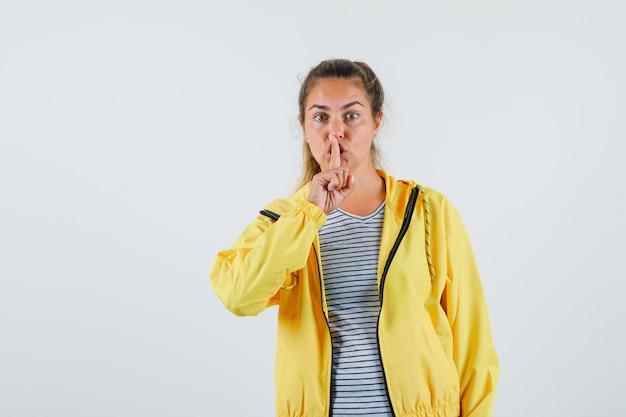 Молодая женщина показывает жест молчания в куртке, футболке и смотрит осторожно. передний план.