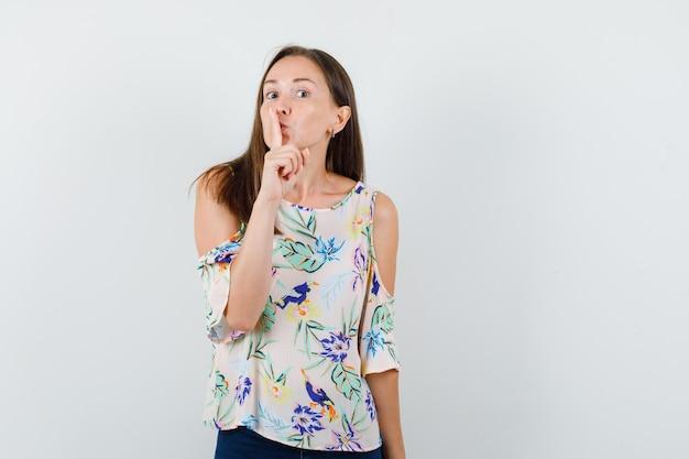 シャツ、ジーンズで沈黙のジェスチャーを示し、注意深く見ている若い女性。正面図。
