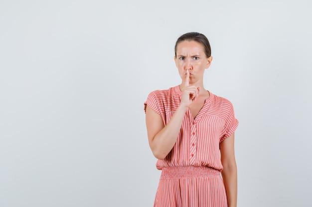 縞模様のドレスで沈黙のジェスチャーを示し、真剣に見える若い女性。正面図。