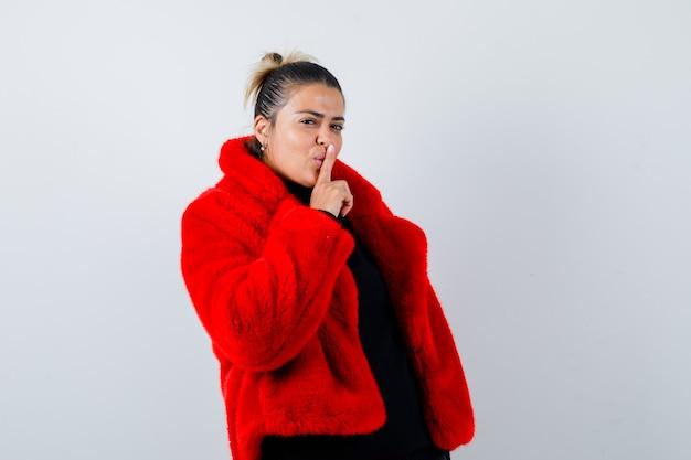 Молодая женщина показывает жест молчания в свитере, красной шубе и выглядит уверенно, вид спереди.