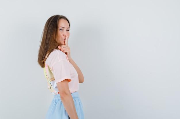Tシャツ、スカートで沈黙のジェスチャーを示し、注意深く見ている若い女性。