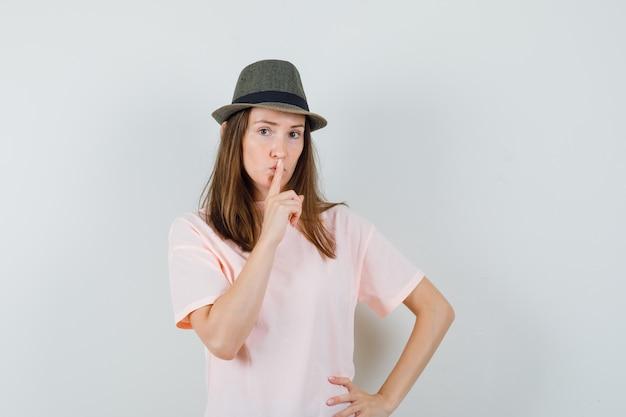 Giovane femmina che mostra il gesto di silenzio in maglietta rosa, cappello e guardando attento, vista frontale.