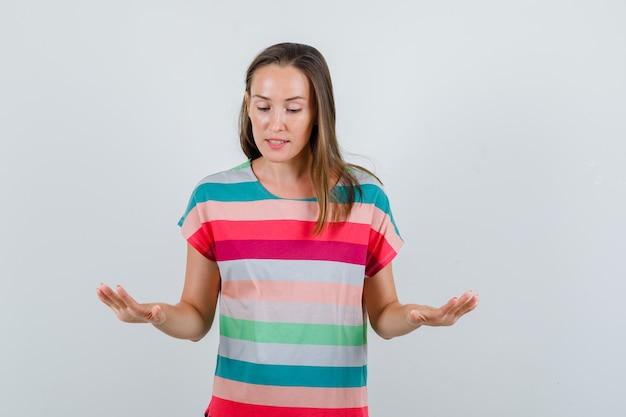 Giovane femmina che mostra rallenta il gesto in t-shirt e sembra calma, vista frontale.